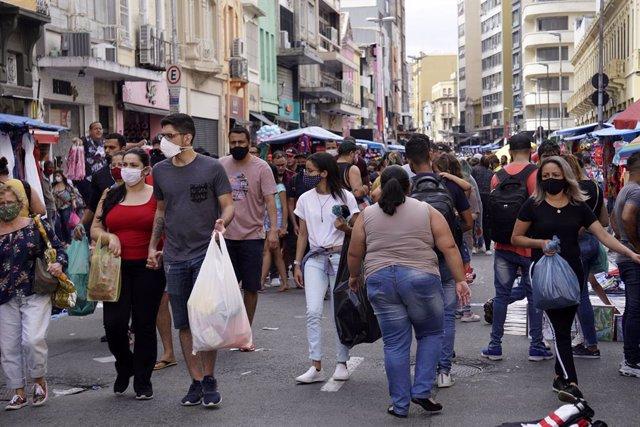 Archivo - Un grupo de personas camina en una de las zonas comerciales de Sao Paulo.