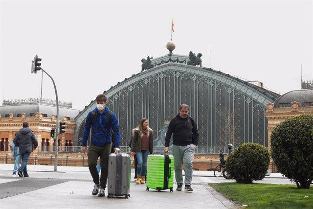 Archivo - Varios turistas con maletas se protegen con mascarillas a su salida de la Estación de Atocha.