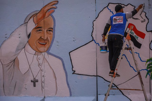 """21 February 2021, Iraq, Baghdad: Amjad, an Iraqi artist from the """"Imprint of Hope"""" NGO, paints a mural of Pope Francis on the wall surrounding the Sayidat al-Nejat (Our Lady of Deliverance) Syriac Catholic Church. Pope Francis is scheduled for a visit to"""