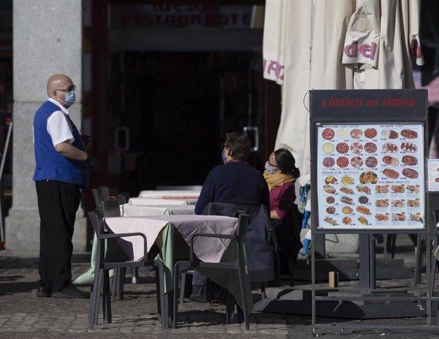 Archivo - Un camarero atiende la terraza de un establecimiento ubicado en la Plaza Mayor