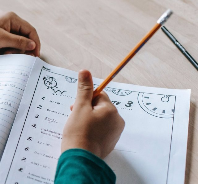 Un alumno hace los deberes en el cuaderno.