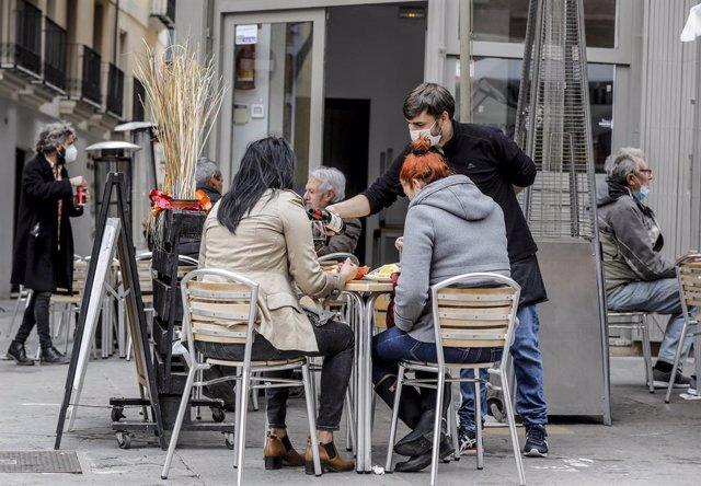 Un cambrer atén a dos clientes en una terrassa el primer dia de l'obertura de l'hoteleria a València en la desescalada de la tercera ona