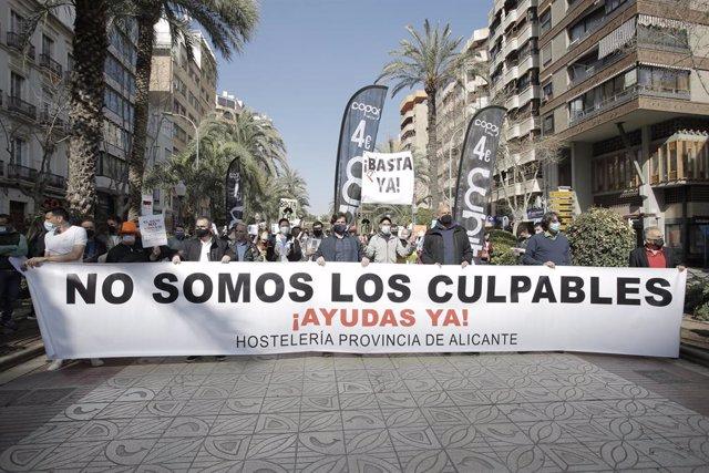 """Hosteleros de Alicante participan en una manifestación con una pancarta donde se puede leer """"No somos los culpables, ¡Ayudas ya!"""" como signo de protesta para denunciar el fracaso del Plan Resiste y la necesidad de la reapertura."""
