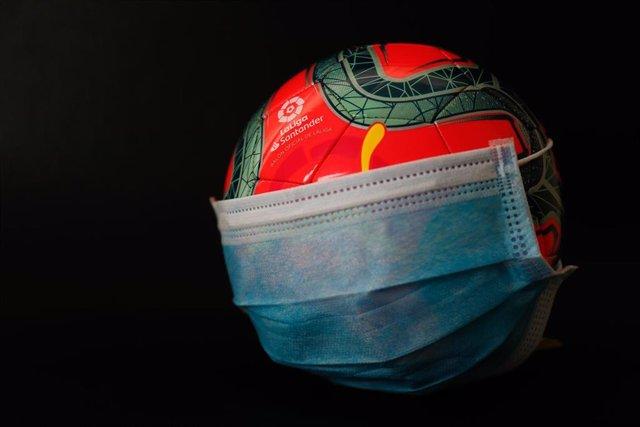 Archivo - Una pelota oficial de invierno de la Liga con una mascarilla quirúrgica.