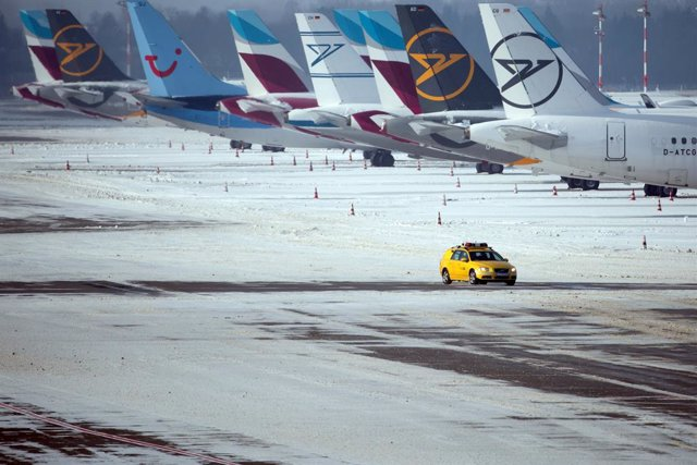 09 February 2021, North Rhine-Westphalia, Düsseldorf: An airport security vehicle drives across a snow-covered apron in Dusseldorf Airport next to parked aircraft. Photo: Federico Gambarini/dpa