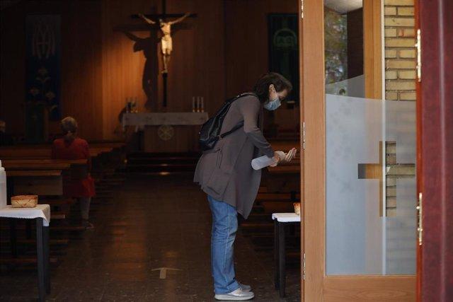 Archivo - Una mujer utiliza el gel hidroalcohólico en la entrada de una parroquia.