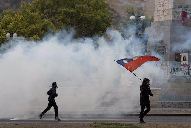 Dos manifestantes corren entre el humo de los botes lanzados por la Policía en una manifestación en Santiago de Chile.