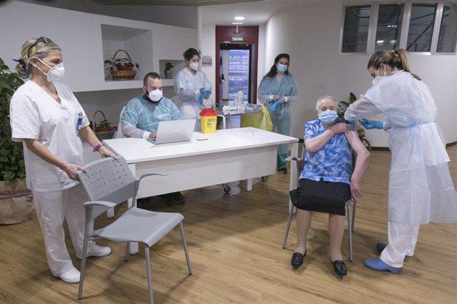 Archivo - Una mujer mayor recibe la vacuna contra el coronavirus en el Centro Polivalente de Recursos Residencia Mixta de Gijón.