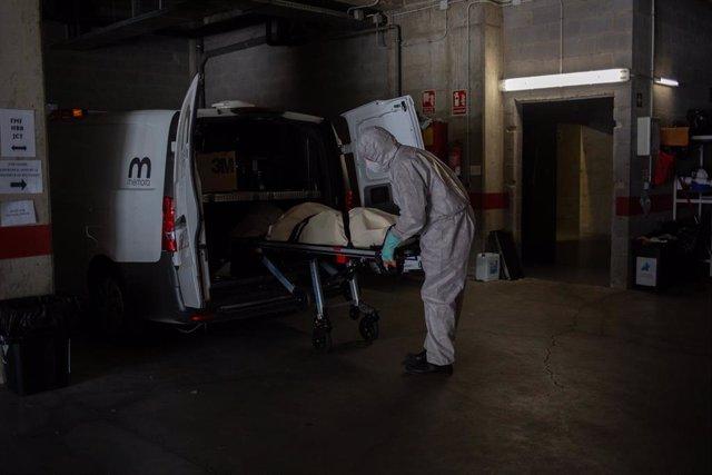 Archivo - Varios operarios protegidos de los Servicios Funerarios Memora trasladan un cuerpo de una residencia  en la primera ola de la pandemia.