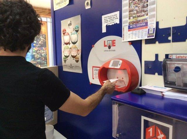 Archivo - Un apostante en una administración de loterías