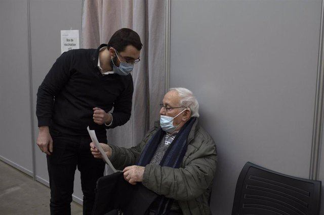 Un anciano hace una consulta mientras espera su turno para vacunarse.