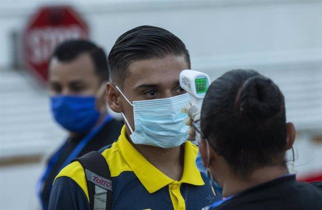 Archivo - Toma de temperatura a un hombre en Managua.