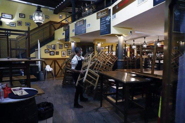 Archivo - Un camarero se afana en recogen la terraza del bar