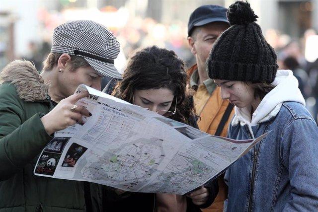 Archivo - Un grupo de turistas consultan un mapa de la ciudad de Madrid.
