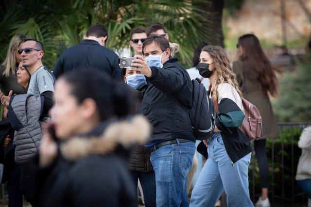 Archivo - Dos personas se hacen un selfie y otra camina en una zona cercana a la Sagrada Familia, en una imagen de archivo
