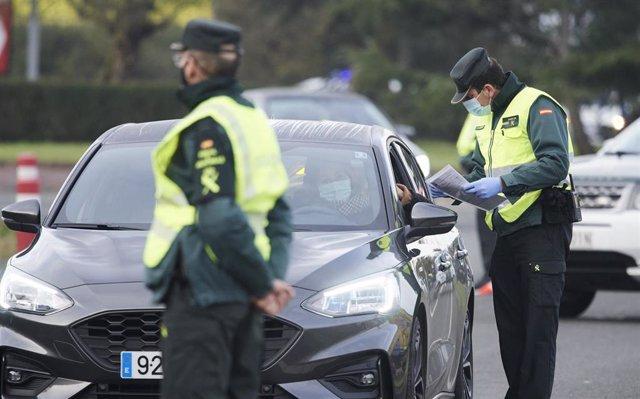 Archivo - Un agente de la Guardia Civil pide la documentación a un vehículo durante un control efectuado en Cantabria.