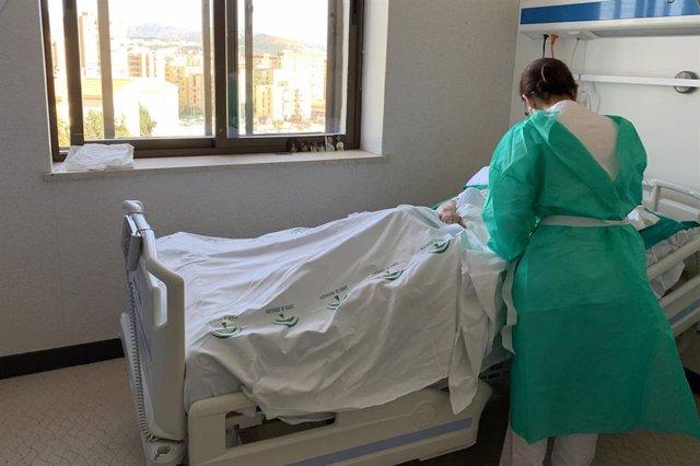 Archivo - Una profesional sanitaria atiende a un paciente en el Hospital Regional de Málaga