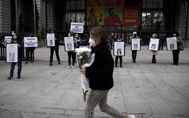 Una mujer pasa por delante de una manifestación ante el Ministerio de Consumo para exigir el cierre de las páginas de pornografía