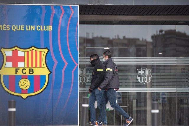 Dso personas entran por una de las puertas del Camp Nou, Barcelona, Catalunya (España), a 1 de marzo de 2021. Agentes del Área Central de Delitos Económicos de la División de Investigación Criminal de los Mossos d'Esquadra están registrando durante la mañ