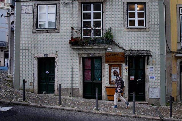 Una mujer con mascarilla pasea en Lisboa