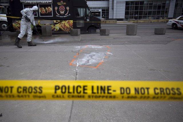 Archivo - Un hombre limpia tras el cordón policial que marcaba la escena del atropello realizado por Alek Minassian en Toronto.
