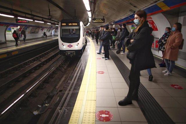 Varios pasajeros esperan en un andén de metro de la estación de Sol de Madrid