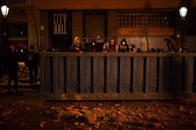 Manifestants que donen suport a Pablo Hasél mouen mobiliari urbà durant els aldarulls a Barcelona (Espanya), 17 de febrer del 2021.