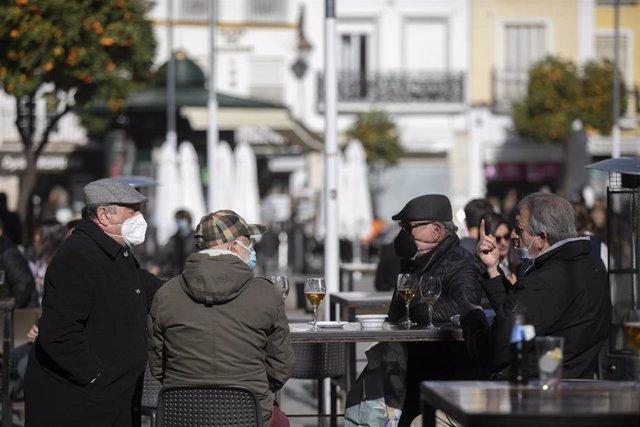Archivo - Personas en la terraza de un bar, en Sevilla