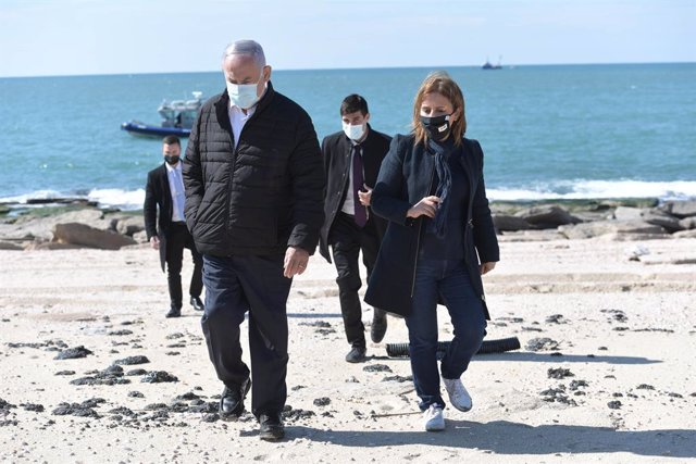 HANDOUT - 21 February 2021, Israel, Ashdod: Israeli Prime Minister Benjamin Netanyahu (L) and Israeli Minister of Environmental Protection Gila Gamliel tour the beach in Ashdod in light of the tar pollution and the subsequent ecological damage. Photo: Kob