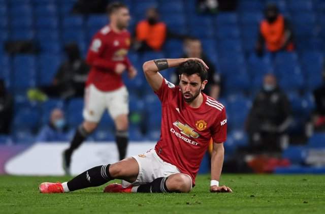 28 February 2021, United Kingdom, London: Manchester United's Bruno Fernandes stays down after a challenge during the English Premier League soccer match between Chelsea and Manchester United at Stamford Bridge. Photo: Andy Rain/PA Wire/dpa