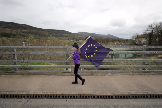 """Archivo - FILED - 30 March 2019, Northern Ireland, Carrickcarnon: A girl holds an EU flag during a protest organized by the organisation """"Border Communities Against Brexit"""". Photo: Niall Carson/PA Wire/dpa"""