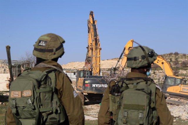 Soldados israelíes hacen guardia mientras las excavadoras se preparan para destruir una casa palestina en Cisjordania