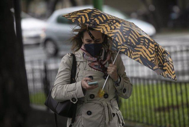 Una mujer camina bajo su paraguas