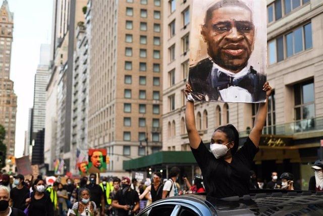 Archivo - Una persona sujeta un retrato de George Floyd en una manifestación contra la violencia policial y el racismo en Estados Unidos.