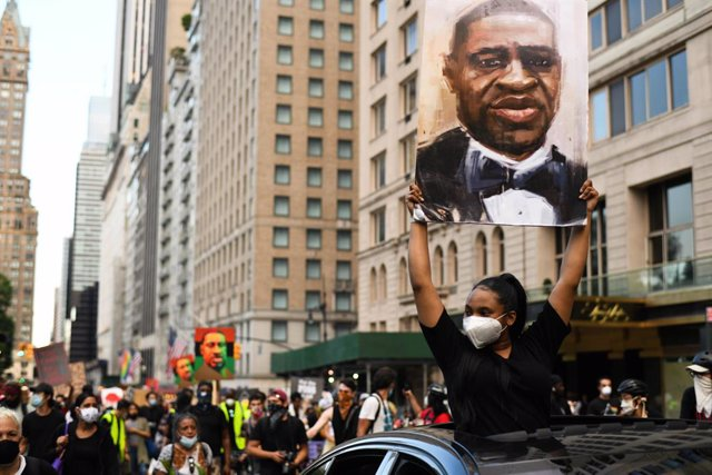 Archivo - 19 June 2020, US, New York: Demonstrators hold pictures of George Floyd, an African American citizen who was killed on 25 May 2020 while in police custody in the US city of Minneapolis, as they march through the streets of Manhattan to commemora