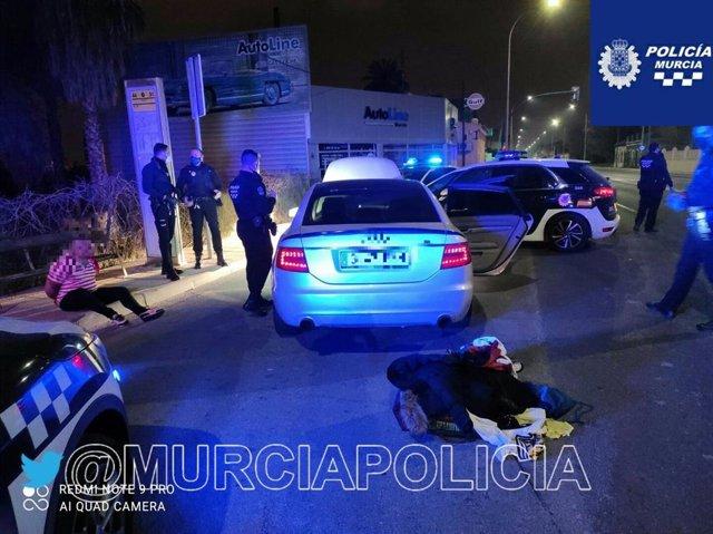 El detenido, sentado en el suelo, con el coche que conducía en primer plano