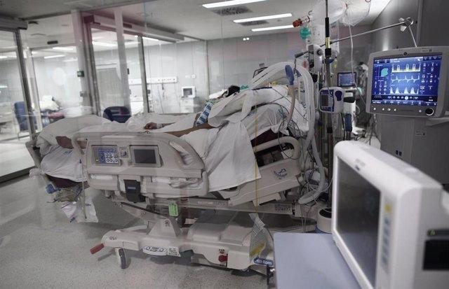 Archivo - Un enfermo en una cama de la UCI.
