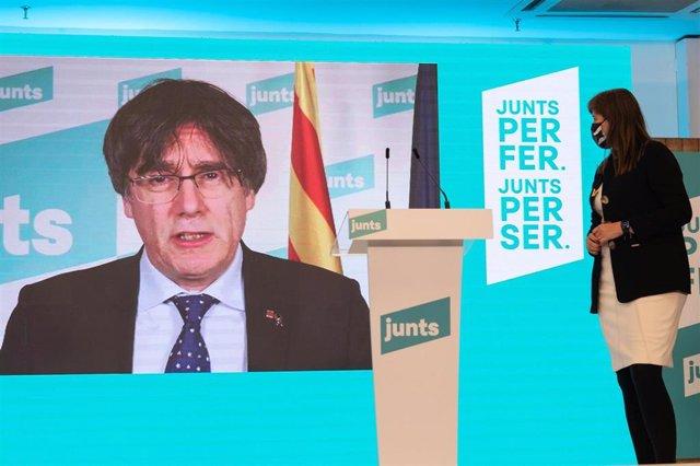 Carles Puigdemont (pantalla), durante una rueda de prensa para valorar los resultados obtenidos por su formación en los comicios catalanes durante la noche electoral del 14-F en la sede de su partido, en Barcelona.