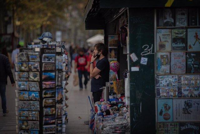 Archivo - Un hombre fuma al lado de un quiosco en Barcelona, Catalunya (España), a 16 de noviembre de 2020. El turismo internacional se desplomó este verano debido como consecuencia del coronavirus. Además, el pasado 15 de octubre el Govern de la Generali