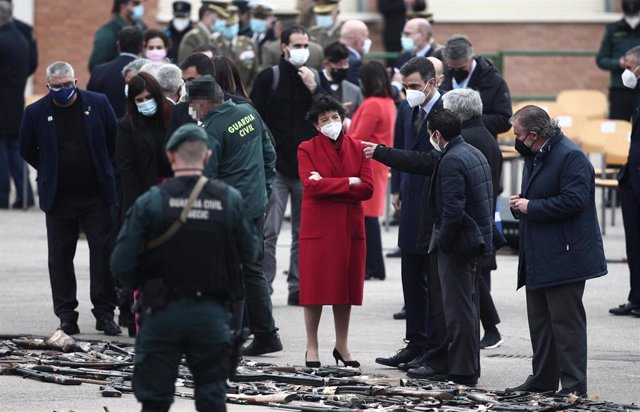 El presidente del Gobierno, Pedro Sánchez (4d), y la ministra de Educación y Formación Profesional, Isabel Celaá (5d), durante un acto de destrucción simbólica de casi 1.400 armas, en el Colegio de Guardias Jóvenes Duque de Ahumada, en Valdemoro, Madrid (