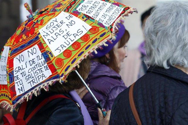 Archivo - Una mujer pega carteles reivindicativos en su paraguas durante la marcha por el Día Internacional de la Mujer en Málaga, (Andalucía, España), a 08 de marzo de 2020. (Foto de archivo).