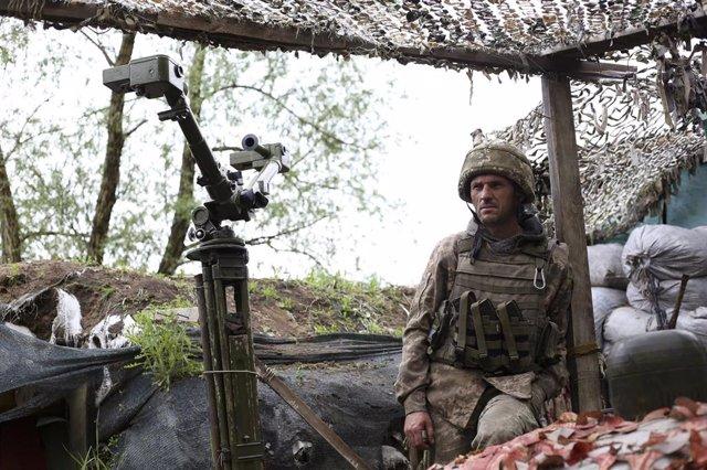 Archivo - Un soldado ucraniano observa la línea de frente desde un bunker en la disputada región del Donbás.