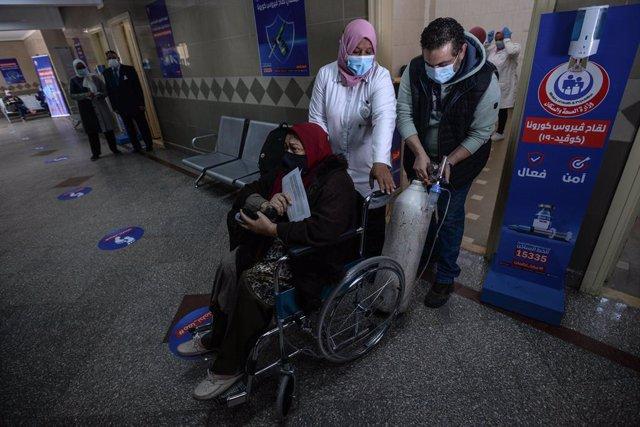 Unos sanitarios ayudan a una anciana a desplazarse para recibir la primera dosis de la vacuna de AstraZeneca contra el coronavirus en el centro medico Qattameya durante la primera jornada masiva de vacunación en Egipto.