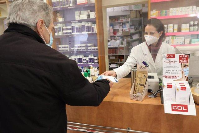 Un anciano recoge una mascarilla FFP2 en la farmacia situada en la C/Tucán (Carabanchel), en Madrid (España), a 4 de febrero de 2021. Los mayores de 65 años de la Comunidad de Madrid pueden recoger a partir de hoy la primera de las dos mascarillas FFP2 qu
