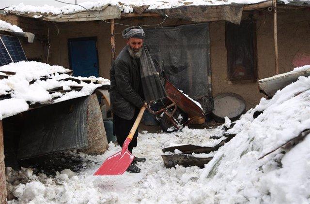 Archivo - Un hombre limpia la nieve en Kabul, capital de Afganistán.