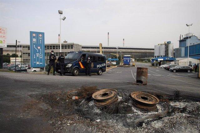 Varios agentes vigilan con un furgón policial en las inmediaciones de la fábrica de Alu Ibérica en A Coruña, Galicia (España), a 4 de marzo de 2021.