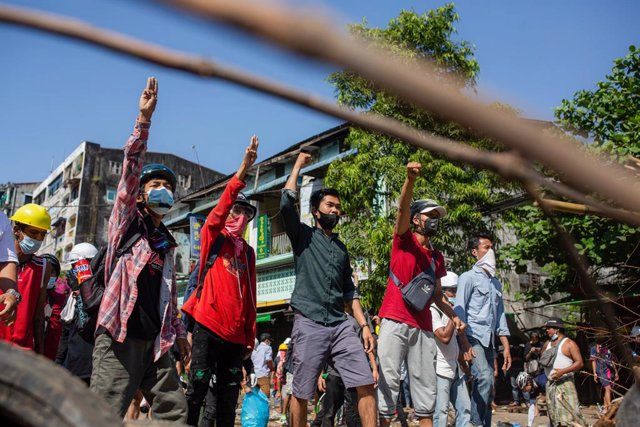 01 March 2021, Myanmar, Yangon: Protesters flash the three finger salute behind a barricade during clashes at a protest against the military coup and detention of civilian leaders in Myanmar. Photo: Aung Kyaw Htet/SOPA Images via ZUMA Wire/dpa