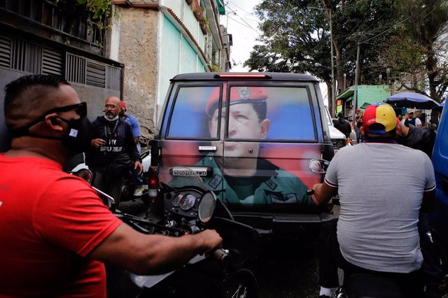 04 February 2021, Venezuela, Caracas: Scooter riders wait behind a vehicle marked with a photo of the late president and leader of the 1992 military uprising, Hugo Chavez during a march to commemorate the military uprising of 4 February 1992. Photo: Jesus