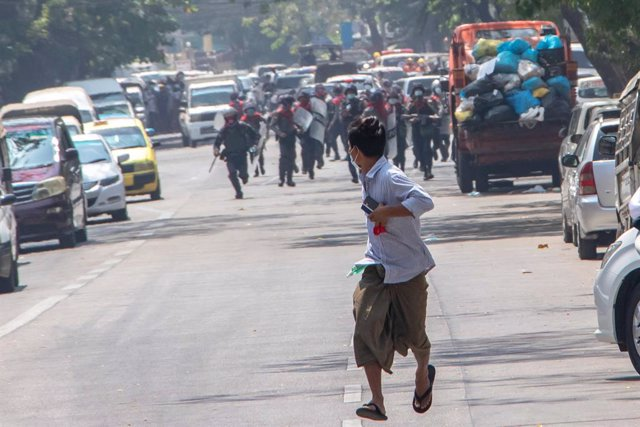 27 February 2021, Myanmar, Rangun: Anti-riot police officers run after a protester during a protest against the military coup and detention of civilian leaders in Myanmar. Photo: Santosh Krl/SOPA Images via ZUMA Wire/dpa