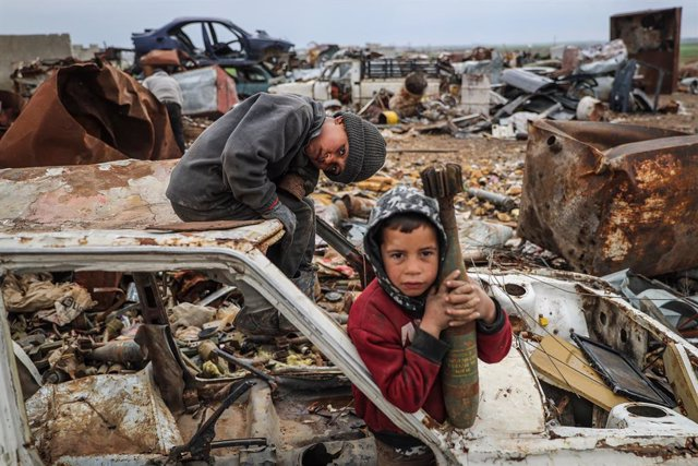 02 March 2021, Syria, Idlib: Malik Junaid (L), 9-years-old, sits on top of a destroyed car next to the 7-years-old Abdel Karim Hassan who carries a mortar shell, at a centre run by Junaid family for selling remnants of shellings and unexploded ordnances,